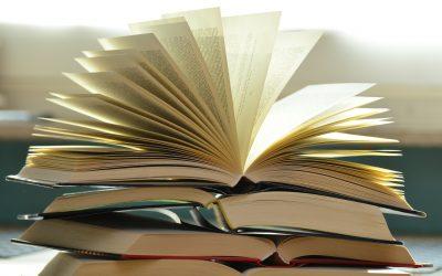 Åpnet bok oppå bokhaug